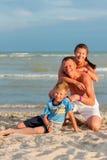 Mamma e figlio del papà sulla spiaggia che ridono e che abbracciano Immagine Stock
