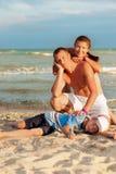 Mamma e figlio del papà sulla spiaggia che ridono e che abbracciano Immagini Stock