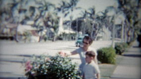 1959: Mamma e figlio della via allineata albero come vecchi passaggi classici dell'automobile Miami, Florida archivi video