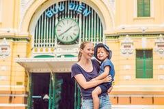 Mamma e figlio sull'ufficio postale centrale di Saigon del fondo sul fondo del cielo blu in Ho Chi Minh, Vietnam Iscrizione in vi immagini stock