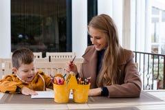 Mamma e giovane matite colorate del ragazzo tiraggio fotografia stock libera da diritti