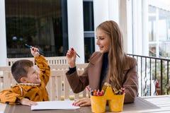 Mamma e giovane matite colorate del ragazzo tiraggio fotografie stock
