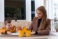 Mamma e giovane matite colorate del ragazzo tiraggio immagini stock