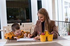 Mamma e giovane matite colorate del ragazzo tiraggio immagine stock