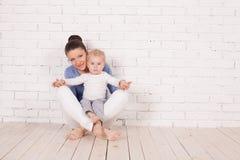 Mamma e giovane ragazzo che si siedono sul pavimento fotografie stock libere da diritti