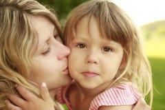 Mamma e la sua piccola figlia su erba Immagine Stock