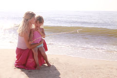 Mamma e la sua piccola figlia sulla spiaggia fotografia stock libera da diritti