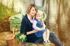 Mamma e piccola figlia adorabile che giocano insieme nella vecchia b di legno Fotografia Stock