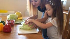 Mamma e piccola figlia nel cavolo del taglio della cucina per un'insalata vegetariana Assistente del ` s della mamma stock footage