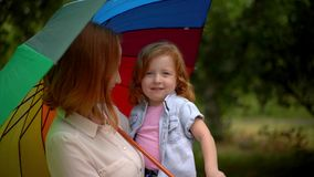 Mamma e ragazza sotto l'ombrello colorato in natura video d archivio