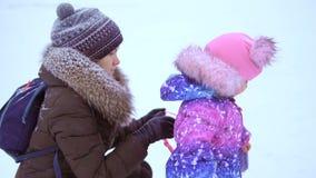 Mamma e sua figlia di tre anni La mamma aiuta un piccolo bambino grazioso a decollare lo zaino stock footage