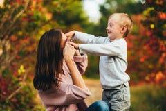 Mamma ed abbraccio e risata del figlio nel parco di autunno Spazio per testo immagine stock libera da diritti