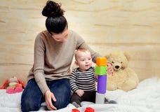 Mamma ed il suo bambino sveglio che giocano con i blocchi di plastica Fotografia Stock