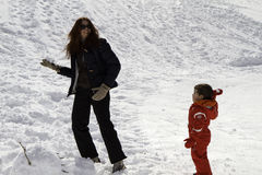 Mamma en baby met rood skikostuum in de sneeuw royalty-vrije stock foto