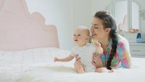Mamma en babyjongen het spelen in de slaapkamer in de ochtend stock footage