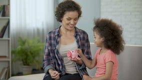 Mamma en de dochter die muntstukken het werpen in spaarvarken, die geld besparen voor stellen voor stock videobeelden