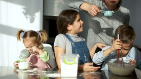 Mamma en de jonge geitjes in de keuken Drie kinderen kneden het deeg en spelen met bloem De grap, pret, leert hoe te om wanneer t stock videobeelden