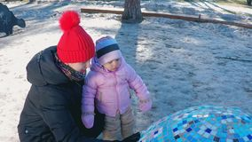 Mamma en dochter dichtbij de installatie-eieren op de speelplaats in een park met lange pijnbomen in de vroege lente wordt geboge stock footage