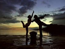 Mamma en dochter die in de zonsondergang dansen Stock Afbeelding
