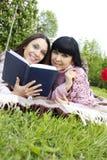 Mamma en dochter die een boek lezen Stock Foto's