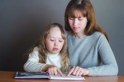 Mamma en dochter die een boek lezen Royalty-vrije Stock Afbeeldingen