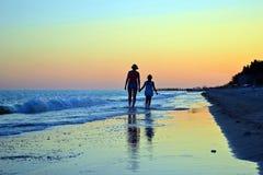 Mamma en dochter die op het lege vreedzame overzeese strand bij zonnen lopen Stock Afbeelding