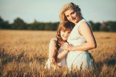 Mamma en dochter die pret door het meer, gebied hebben die in openlucht van aard genieten Royalty-vrije Stock Foto's