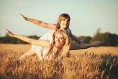 Mamma en dochter die pret door het meer, gebied hebben die in openlucht van aard genieten Stock Fotografie