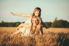 Mamma en dochter die pret door het meer, gebied hebben die in openlucht van aard genieten Stock Foto's