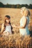 Mamma en dochter die pret door het meer, gebied hebben die in openlucht van aard genieten Stock Afbeeldingen