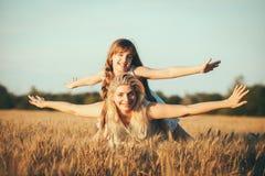 Mamma en dochter die pret door het meer, gebied hebben die in openlucht van aard genieten Stock Afbeelding