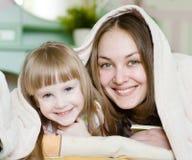 Mamma en dochter die pret hebben onder de deken royalty-vrije stock afbeelding