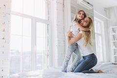 Mamma en dochter die pret hebben thuis Stock Afbeeldingen