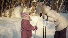 Mamma en dochter die vóór het noordse lopen in de voorsteden in de winter spreken stock video