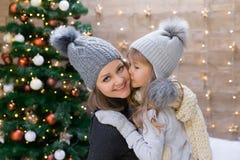 Mamma en dochter, grijze hoed, Kerstboom Stock Foto's