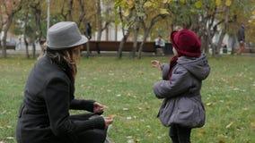 Mamma en dochter in het park die werpend bladeren spelen Stock Fotografie
