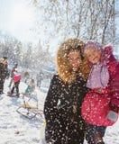 Mamma en dochter in het park onder dalende sneeuw Stock Afbeelding