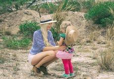 Mamma en dochter in hoeden Mooie blonde vrouw die hoed in openlucht op prairie dragen royalty-vrije stock foto