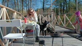 Mamma en dochter, jonge vrouw die in warme kleren een hamburger eten, dichtbij is er een klein meisje met een hond, een picknick  stock video