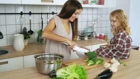 Mamma en dochter kokende groenten bij de keuken stock video