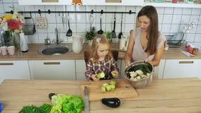 Mamma en dochter kokende groenten bij de keuken stock videobeelden