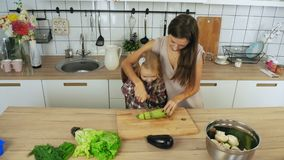 Mamma en dochter kokende groenten bij de keuken stock footage