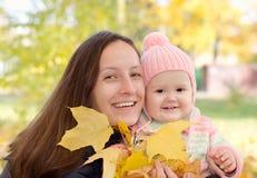 Mamma en dochter met bladeren Stock Afbeeldingen