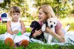 Mamma en dochter met het puppy van Labrador Stock Afbeeldingen