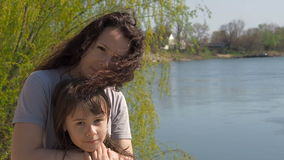 Mamma en dochter op de rivierbank Vrouw met kind op een zonnige dag door het water Gelukkige familie in aard stock video
