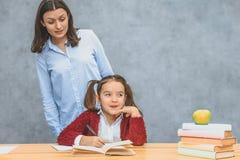 Mamma en dochter op een grijze achtergrond Tegelijkertijd schrijft de schooljongen thuiswerk, moederhorloges haar dochter stock foto's