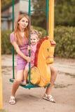 Mamma en dochter op een schommeling in roze stock foto's