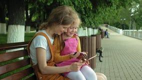 Mamma en dochtergebruiksgadgets in openlucht De zomer stock videobeelden