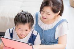 Mamma en dochtergebruikstablet stock afbeeldingen