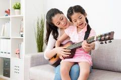 Mamma en dochternadruk op de gitaar Royalty-vrije Stock Afbeeldingen